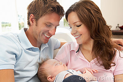 Close Up Of Parents Cuddling Newborn Baby Boy At H