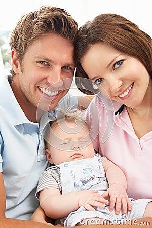 Close Up Of Parents Cuddling Newborn Baby Boy At H