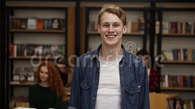Close up portrait attractive young man laughing enjoying successful lifestyle achievement cheerful caucasian male in. Library bookshelf and classmates on stock footage