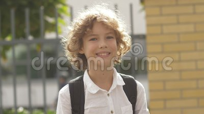 Close up portrait of beautiful , attractive , caucasian curly hair boy with Backpack. School child looking and smiling. On the camera 4K stock video