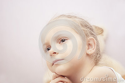 Close up portrait of blond little girl thinking