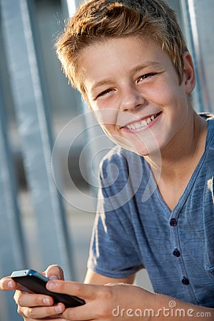 Close up portrait of boy with phone outdoors.