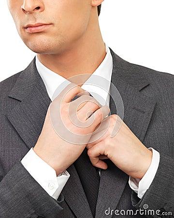 Close up portrait of a business man adjusting tie