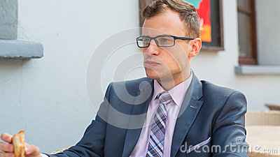 A close-up portrait of a businessman having breakfast.