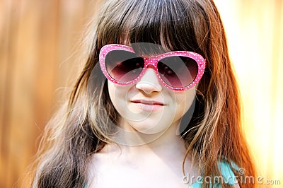 Close-up portrait of child girl in pink sunglasses