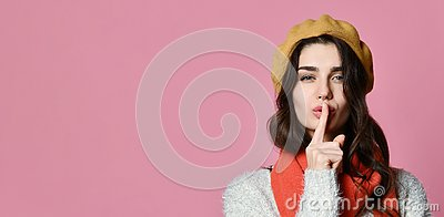 Pretty charming young woman having secret while holding finger on lips and showing silence sign Stock Photo
