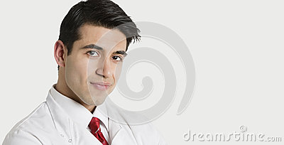 Close-up portrait of a handsome Indian male doctor smiling over light gray background