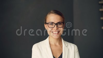Close-up portrait of happy elegant businesswoman looking at camera and smiling wearing glasses and formal style clothing. Close-up portrait of happy elegant stock video footage