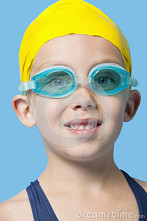 Close-up portrait of a happy young girl wearing swim cap and goggles over blue background