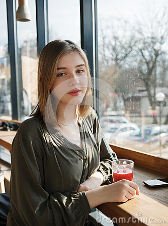 Free Close Up Portrait Of Happy Beautiful Teen Student Girl With A Glass Mug Straw Fruit Tea At Street Cafe Sitting Near Big Window Royalty Free Stock Photos - 90168048
