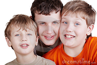 Close-up portrait of three grinning boys