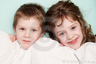 Close-up portrait of two children in bed