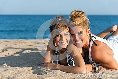 Close up portrait of two girl friends on beach.