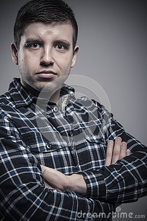 Close up portrait of young composed man wearing checked shirt with arms crossed