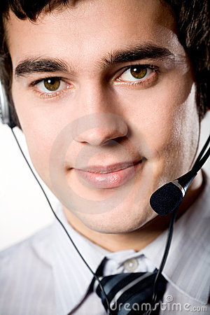 Close-up portrait of young smiling businessman with headset on