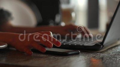 Close-up rear view of young business woman working in office interior on pc holding smartphone and looking at screen. With diagrams. Office person using mobile stock video footage