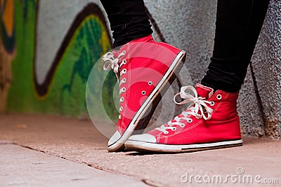 Close up of red sneakers worn by a teenager.