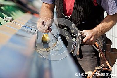 Close-up of a roofer welding the gutter