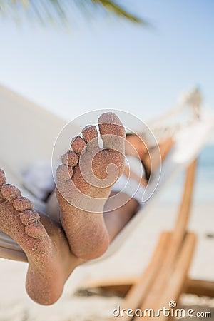Close up of sandy feet of woman sleeping in a hammock