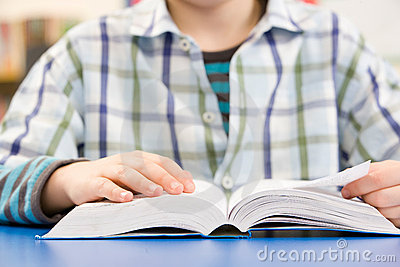 Close Up Of Schoolboy Studying Textbook