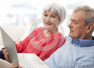 Close-up of a senior couple using laptop