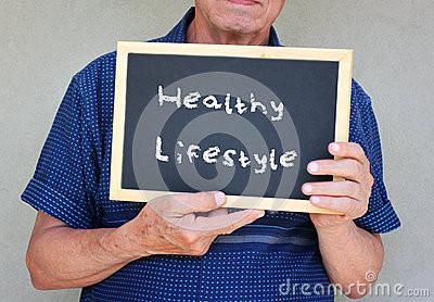 Close up of senior man holding a blackboard with the phrase good health equals good life