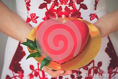 Close up shot of female hands holding golden plate with tasty festive cake shaped like a big red heart Stock Photo