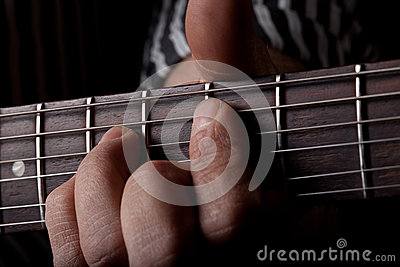 Close up shot of a mans left hand playing guitar