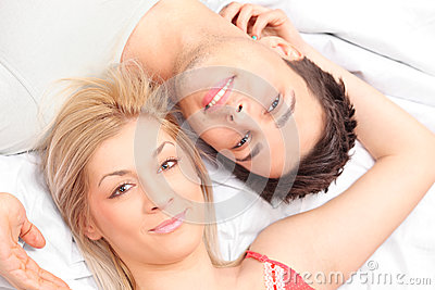 Close-up shot of a young couple laying in a bed