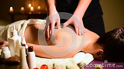Close-up spa de schouders en de rug van de massagevrouw ` s Mannelijke hands do massage aan een vrouw in een donkere ruimte met k stock footage