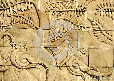 Close up stucco carved wall depicting elephants