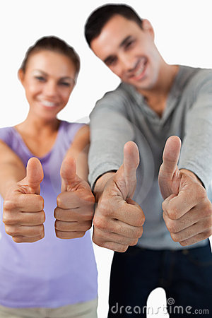 Close up of thumbs up being given by young couple