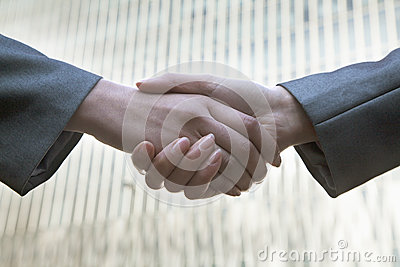 Close up of two business people shaking hands by Chinas world trade center in Beijing
