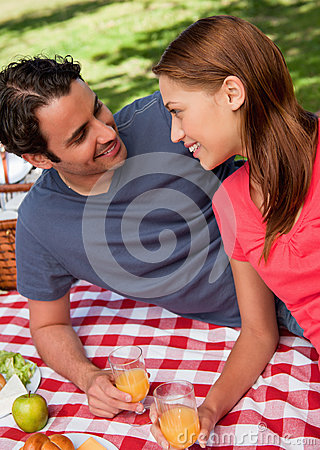 Close-up of two smiling friends lying on a blanket with a picnic