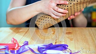 Close-up van de handen die van vrouwen een gift inpakken Ambacht verpakkend document stock video