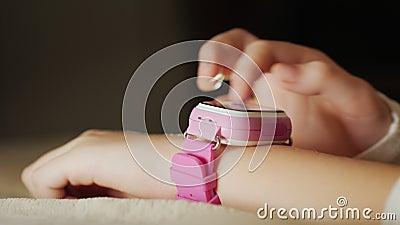 Close-up van een kind` s hand met een roze slim horloge stock videobeelden