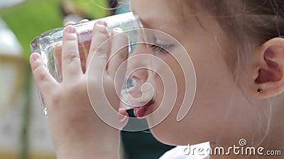 Close-up van een weinig leuk meisje die zuiver water van een glas drinken stock video