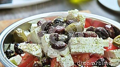 Close-up van manueel het toevoegen van kruiden aan een Griekse plantaardige salade vegetarische keuken Gezond voedsel stock footage