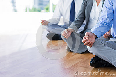 Close up view of business people doing yoga