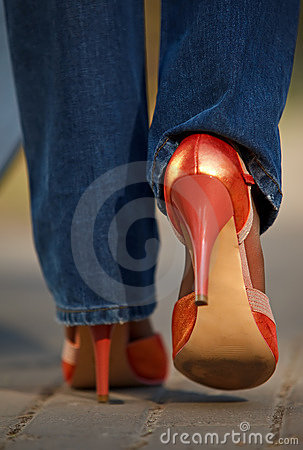 Close-up view of female in red shoes walking