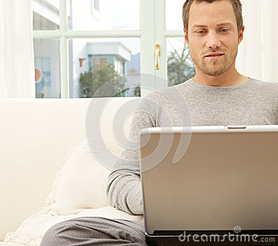 Close up view of professional man with laptop and smart phone at home.