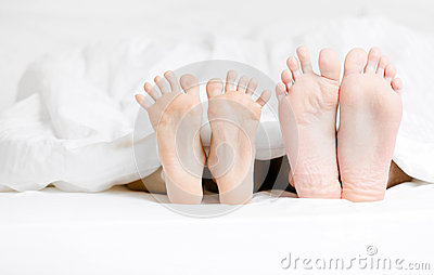 Close up view of feet of the couple lying in bed
