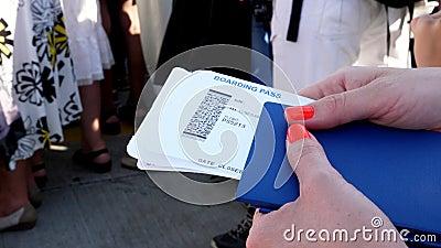Close-up, vrouwelijke handen de kaartjes van de Luchtvaartlijn instapkaart houden, instapkaart en paspoort die bij luchthaven stock footage