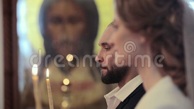 Close up wedding couple in a church with candles at Jesus Christ icon background.  stock footage
