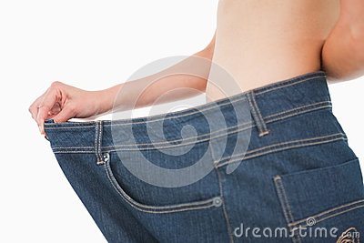 Close-up of a woman belly in too big pants