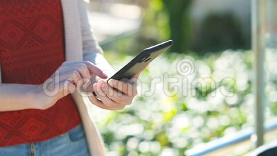 Woman hand using a smart phone in slow motion. Close up of a woman hand using a smart phone in a park in slow motion stock video footage