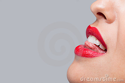 Close up woman licking her red teeth.