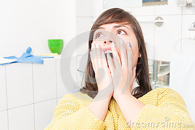 Close-up of woman with open mouth being scared of dentist Stock Photo