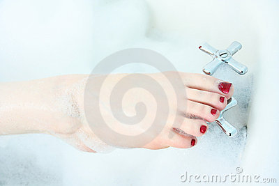 Close-up of woman s foot in bubble bath.