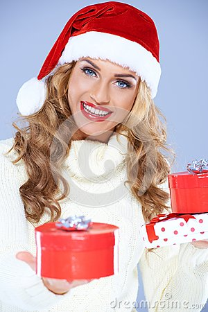 Close up of woman in Santa hat holding gifts